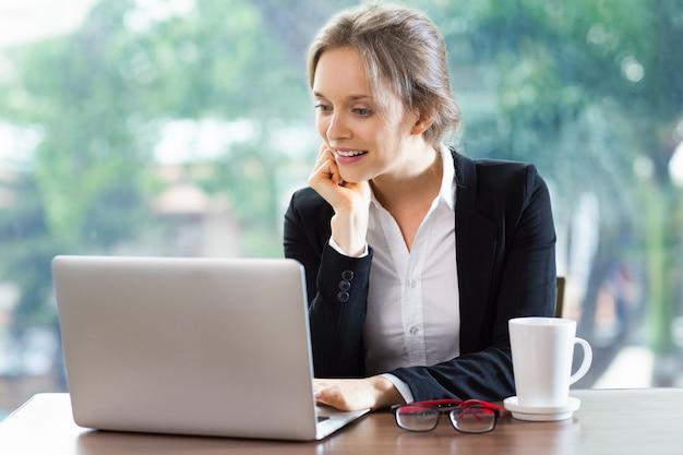ヘッドがラップトップを見て手で休んで笑顔の女性 無料写真