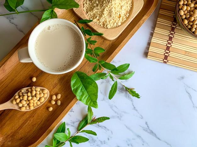 豆乳カップ、木のスプーンに大豆の種、木の板に豆乳粉の平面図 Premium写真