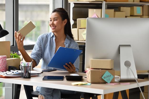 若いアジア女性起業家ビジネスオーナーのオンラインショッピングのために自宅で仕事 Premium写真