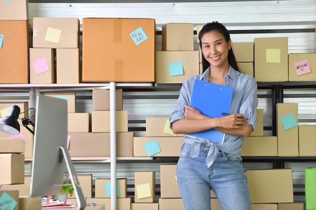 若いアジア女性起業家ビジネスオーナーが自宅でオンラインショッピングとパッケージ製品の準備のために働いて Premium写真