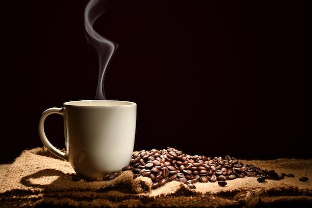 黒い背景に煙とコーヒー豆とコーヒーのカップ Premium写真