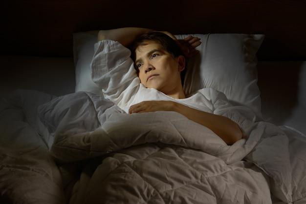 目を開けてベッドに横たわっている不眠症の女性 Premium写真