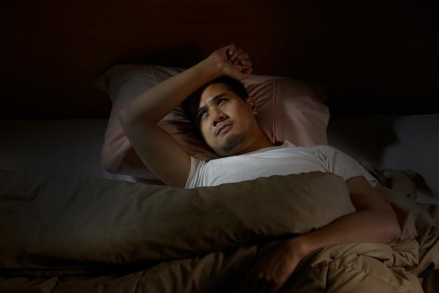 ベッドで横になっている不眠症に苦しんで落ち込んでいる男 Premium写真