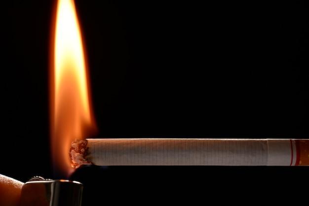 Сигарета горит маленьким пламенем на черном фоне Premium Фотографии