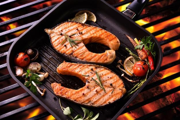 Лосось на гриле с различными овощами на сковороде на гриле Premium Фотографии