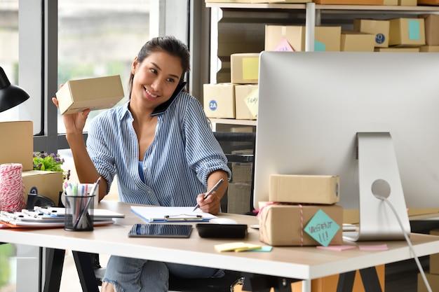 若いアジア女性起業家ビジネスオーナーが自宅のコンピューターでの作業 Premium写真