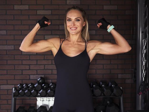 ジムでレンガの壁に対して上腕二頭筋を示すフィットネス女性 Premium写真