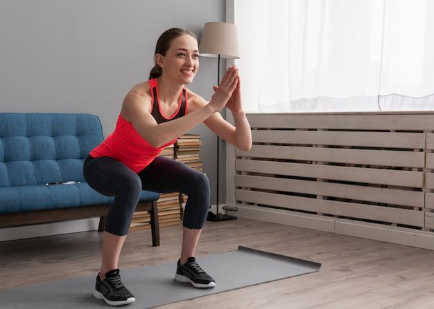 Счастливый фитнес женщина делает приседания на дому Premium Фотографии