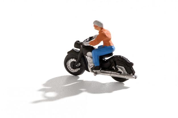 影でバイクに乗るミニ人 Premium写真
