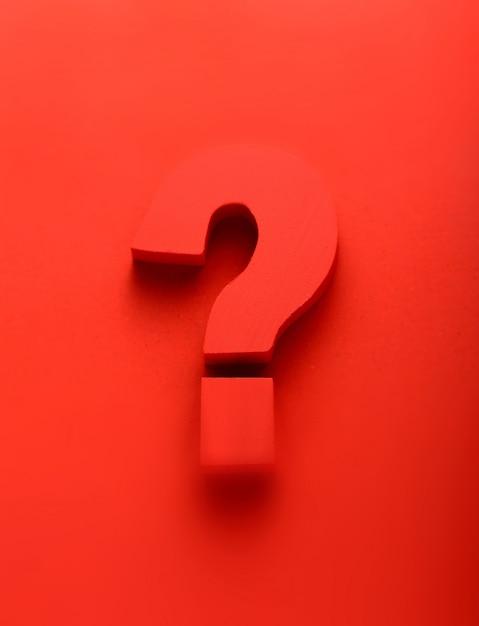 Красный знак вопроса на красном фоне Premium Фотографии
