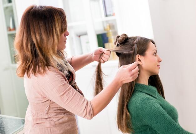 女の子の長い髪をとかす美容院 Premium写真