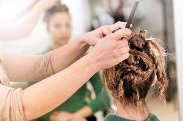 クローズアップで梨花の髪型に取り組んでのヘアスタイリスト Premium写真