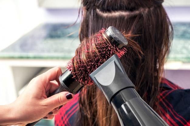 ヘアスタイリストがヘアドライヤーで髪をブラッシング Premium写真