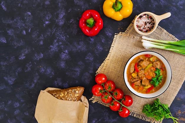 Рагу с мясом и овощами в томатном соусе на темном Premium Фотографии