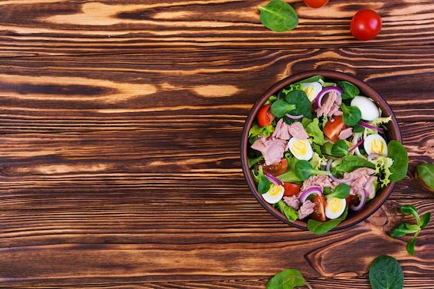 マグロ、トマト、ウズラの卵、アスパラガス、木製の玉ねぎのサラダ Premium写真
