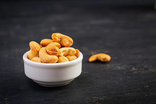 暗い背景の木にカシューナッツ。一握りのナッツ。 Premium写真