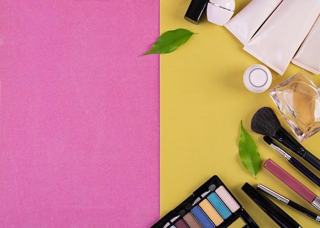 ピンク黄色の背景に化粧品。上面図。コピースペース Premium写真