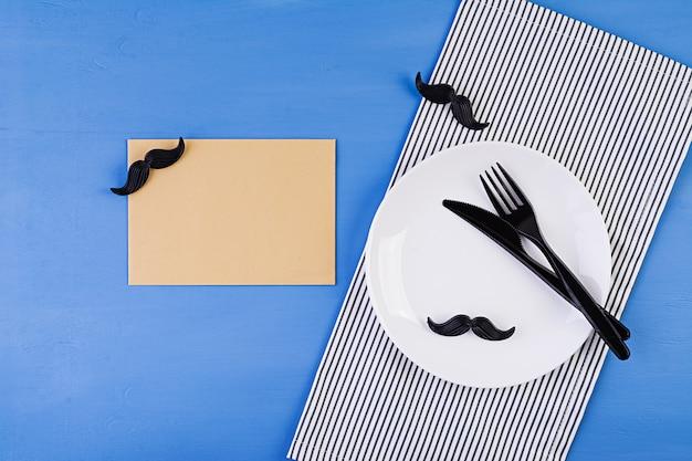 Сервировка стола на день отцов со столовыми приборами и усами. с днем отца. Premium Фотографии