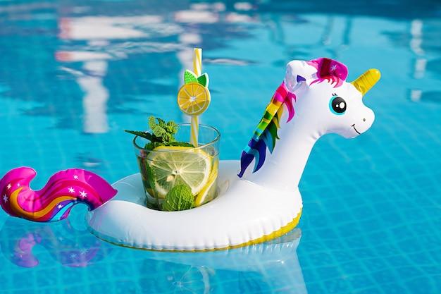 Свежий коктейль мохито на надувной белый единорог игрушка в бассейне. концепция отдыха. Premium Фотографии
