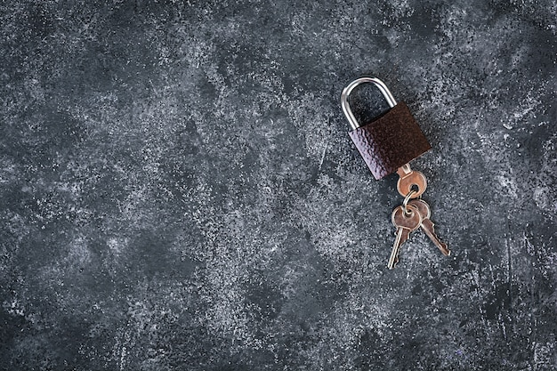 Железный замок с ключами на сером фоне. вид сверху. Premium Фотографии