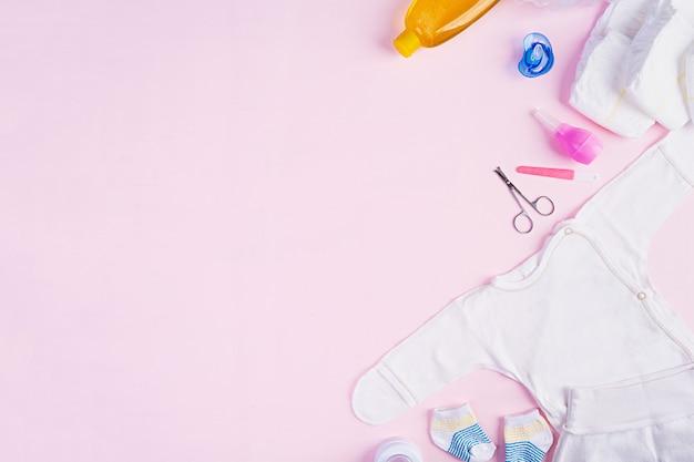 ピンクの背景の子供のためのベビー服やその他のもの。生まれたばかりの赤ちゃんの概念。上面図 Premium写真