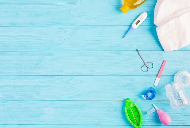 Детская одежда и другие вещи для ребенка на синем фоне. концепция новорожденного. вид сверху Premium Фотографии