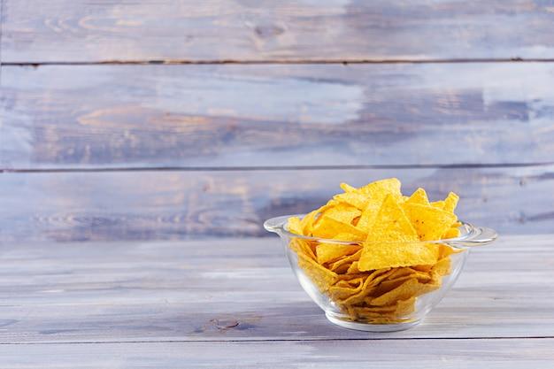 Мексиканские начос с сыром. кукурузные чипсы, изолированные на деревянный стол Premium Фотографии