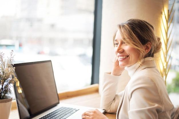 ビジネスランチでラップトップに取り組んでいる白いスイートの女 Premium写真
