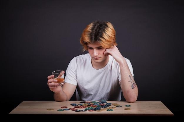 ウイスキーを飲むとポーカーチップを見て若い男の子 Premium写真