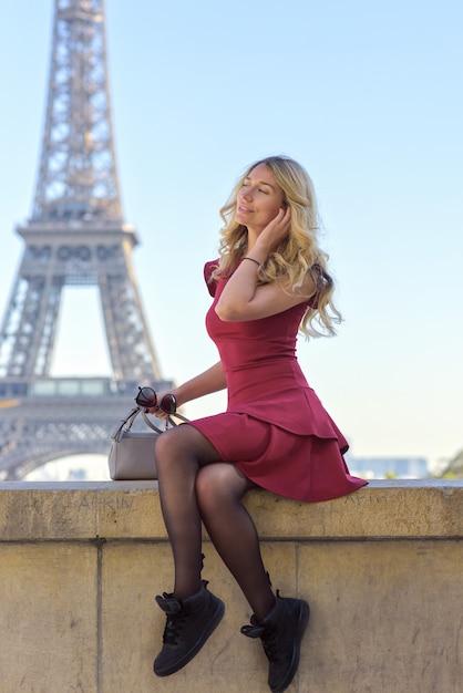 フランスのエッフェル塔で赤いドレスの女 Premium写真