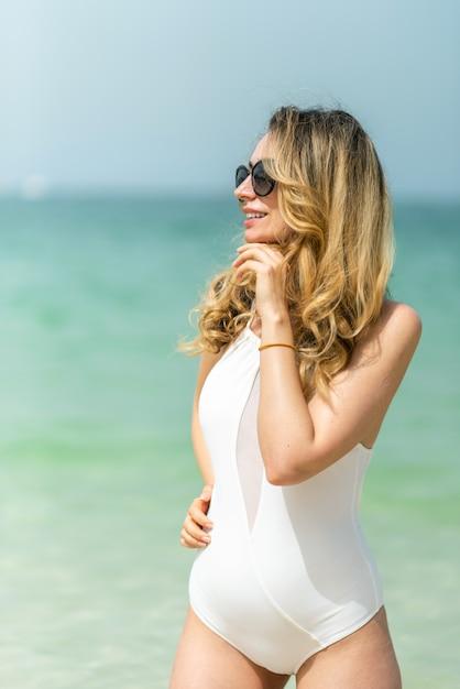 Женщина на пляже дубая в белых купальниках Premium Фотографии