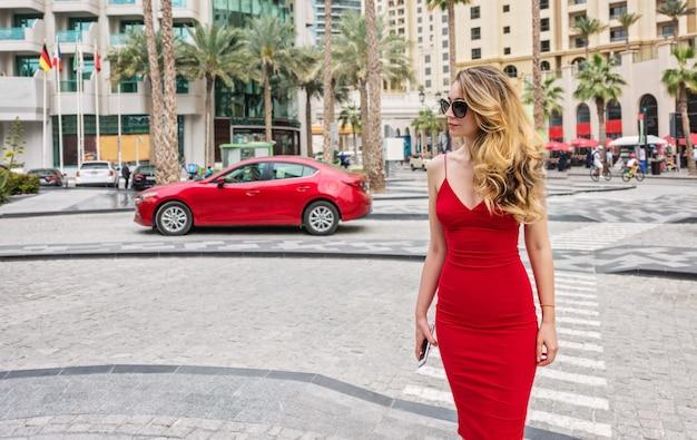 ドバイ、アラブ首長国連邦の女性。赤いドレスを着て魅力的な女性。街の景色を眺める少女 Premium写真
