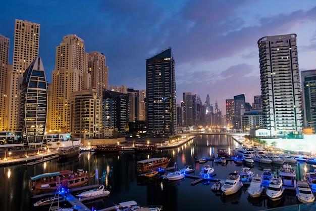 Дубай марина с лодки и здания ночью, объединенные арабские эмираты Premium Фотографии