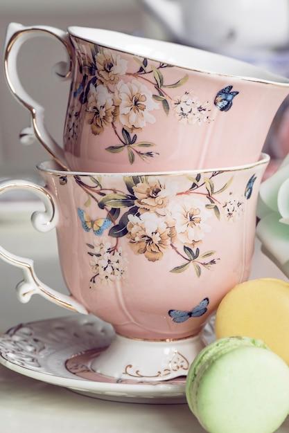 花飾りとマカロンのお菓子とピンクのティーカップ Premium写真