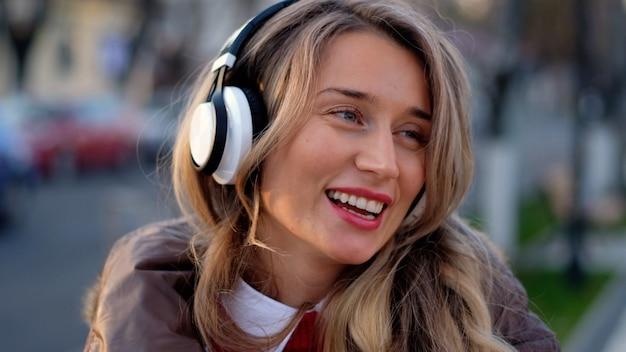 Счастливая женщина слушает музыку на беспроводные наушники Premium Фотографии