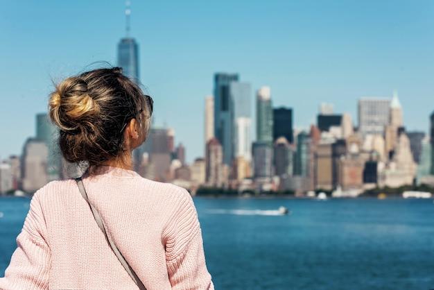 ニューヨークでポーズをとるピンクのセーターの女性 Premium写真