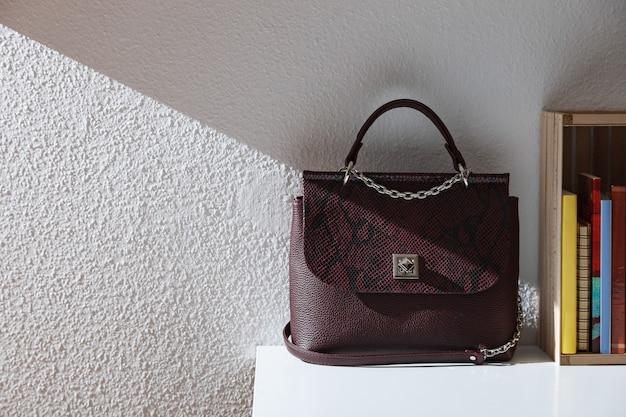 本の横にあるテーブルの上の女性のバッグ Premium写真