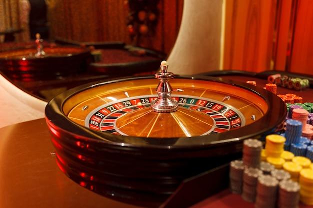 Рулетка, фишки и мяч для казино в интерьере клуба. Premium Фотографии