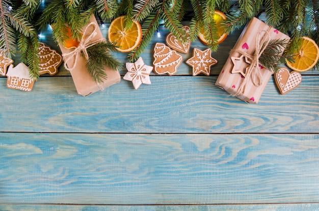木の枝と白い木製の背景にクリスマスプレゼント。 Premium写真