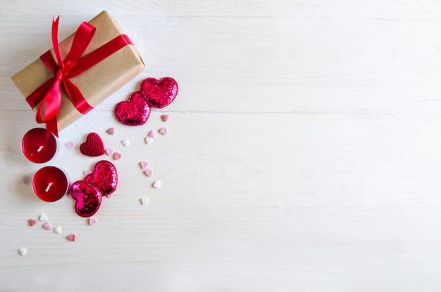 赤いハート、ギフト、キャンドルでバレンタインデーの木製の背景。バレンタインデーのギフト。白い木製の背景 Premium写真