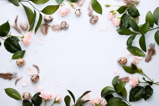 イースターのコンセプトです。テキストのための場所でホワイトウォールに羽、枝、芽のバラとウズラの卵とバナーのサークルフレームのイースター。上面図。フラット横たわっていた。春休みはがき Premium写真