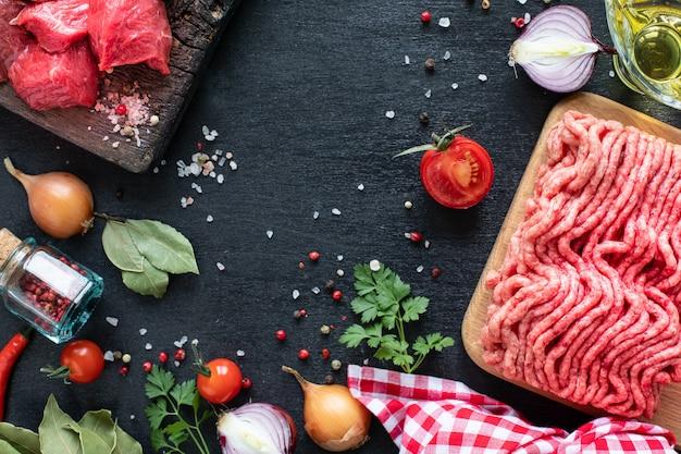 チェリートマト、トウガラシ、ハーブを添えた木製のまな板の上に、仔牛の切り身とひき肉を入れます。 Premium写真
