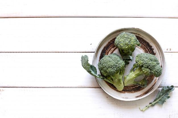 新鮮な緑のブロッコリーとプレート、白い木製の素朴な質感の上から撮影 Premium写真