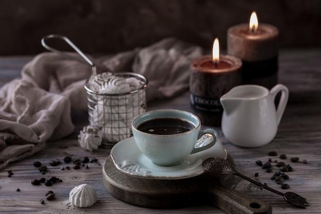 チョコレートチップクッキー、マシュマロ、ろうそくとコーヒーカップ。 Premium写真