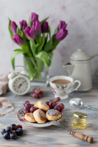 Творожный десерт, чизкейки на столе с букетом тюльпанов, часы и фрукты на деревянном столе у окна. Premium Фотографии