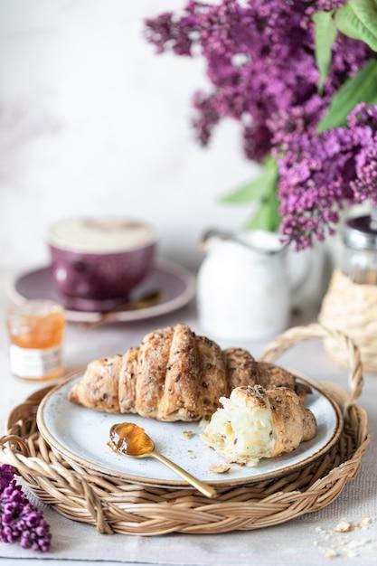 Завтрак французский круассан, джем, чашка кофе, молоко с кремом и сиреневые цветы. утро Premium Фотографии