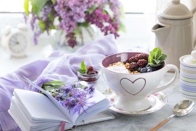 ライラックの花束と窓の近くのテーブルの上の果実とホームグラノーラ。 Premium写真