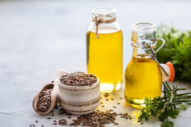 Льняное масло в бутылке и керамической миске с коричневыми семенами льна и деревянной ложкой Premium Фотографии