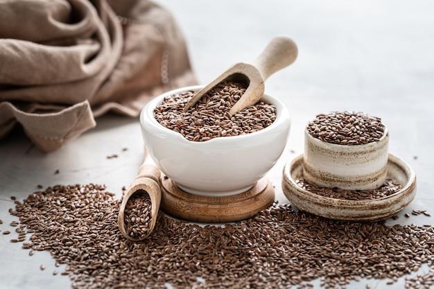 木のスプーンでセラミックボウルに亜麻の種子。有機健康食品。 Premium写真