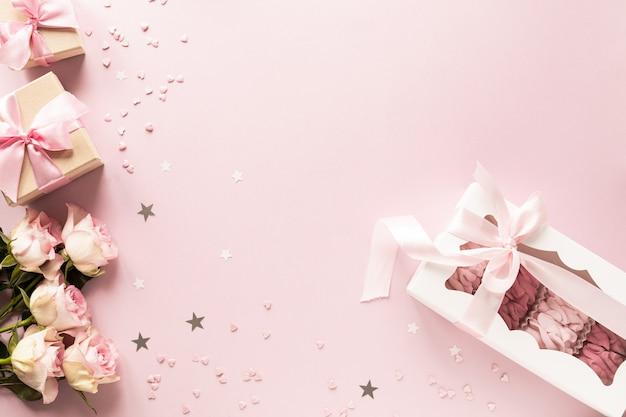 Подарочная коробка или подарочная коробка и цветы на розовом столе вид сверху. Premium Фотографии
